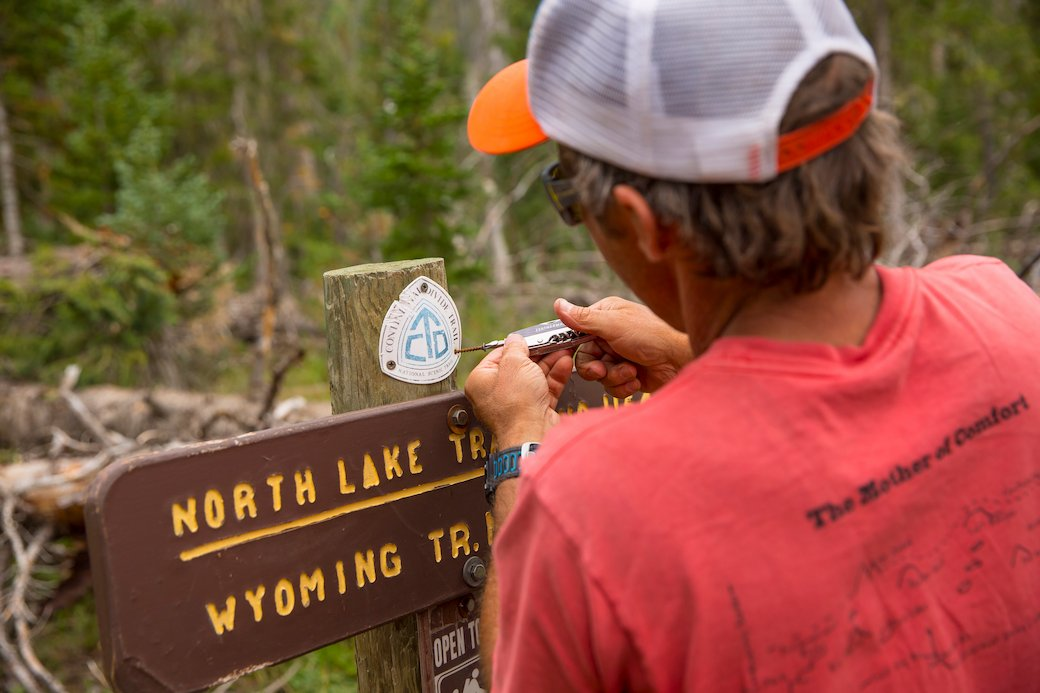 Bill Gamber, co-founder of Big Agnes, places a CDT marker on a trail sign along the CDT in North Routt, CO.
